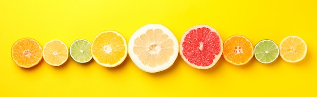 Flat lay with citrus fruits on yellow background, space for text
