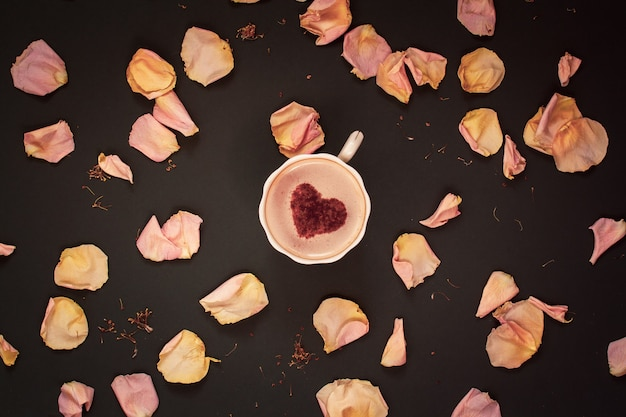 Плоская кладка с кофейной кружкой со сливками и корицей в форме сердца с розовыми лепестками цветов на темном