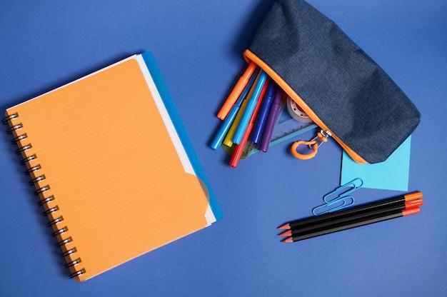 コピースペースのある青い背景に分離された青とオレンジのコントラストの影で、コピーブック、オーガナイザー、カラフルな鉛筆、学用品が落ちるペンケースを備えたフラットレイ。ハイアングルビュー
