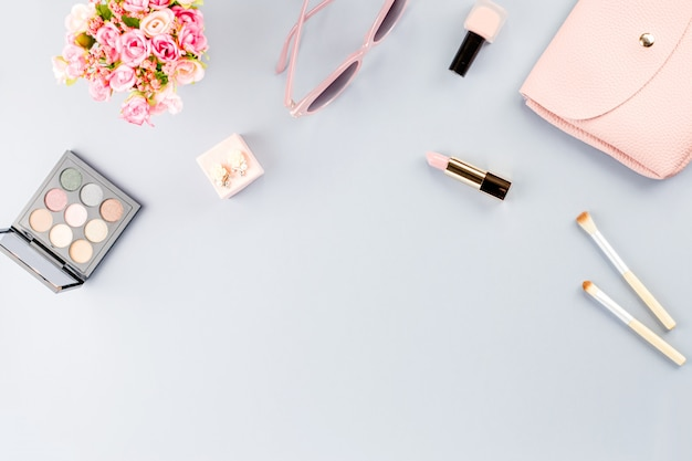 Flat lay with cosmetics, purse, planner book and flowers.