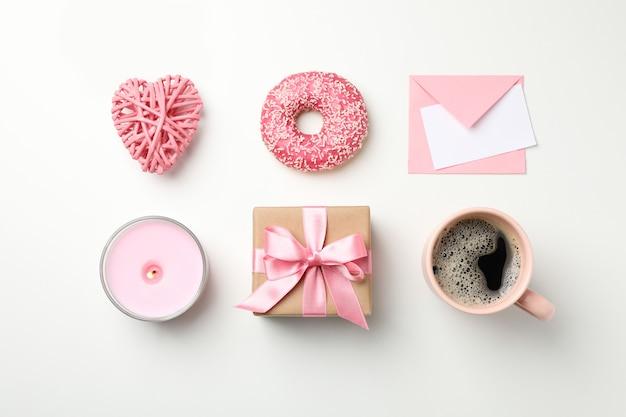 Квартира лежала с чашкой кофе, пончик, подарок, свеча, конверт и сердце на белом фоне, вид сверху
