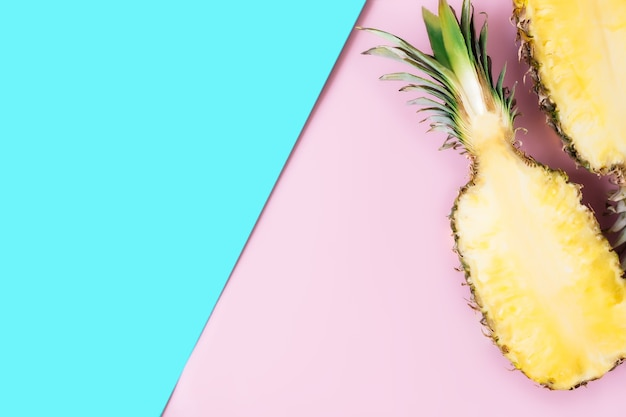 Flat lay with cut halves of fresh pineapple on a pastel pink and blue background. ingredient for pina colada. exotic fruit. high quality photo