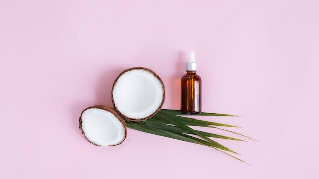 코코넛과 녹색 야자 잎, 파스텔 핑크 표면에 에센셜 오일이 든 유리 병의 절반을 잘라 평평한 평평하게하십시오.