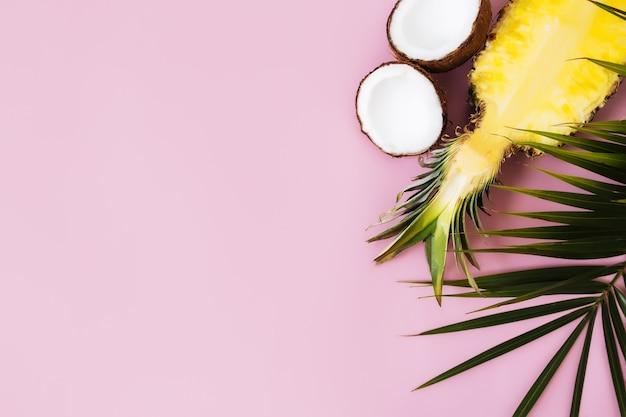 パステルピンクの背景に新鮮なパイナップル、ココナッツ、緑のヤシの葉の半分をカットしたフラットレイ。ピニャコラーダの成分。エキゾチックなフルーツ。