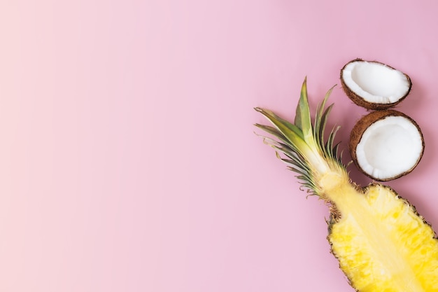 パステルピンクの背景に新鮮なパイナップル、ココナッツの半分をカットしたフラットレイ。ピニャコラーダの成分。エキゾチックなフルーツ。