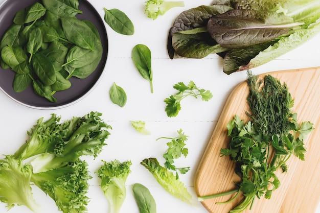 커팅 보드와 신선한 그린 샐러드 그릇 플랫 누워 시금치와 양상추, 로메인과 파슬리, 흰색 바탕에 바 질 잎. 건강한 식생활 개념