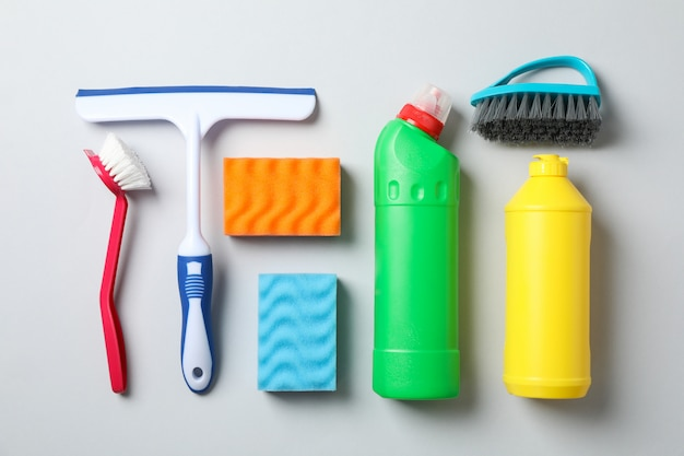 Flat lay with detergents and cleaning supplies on grey, top view