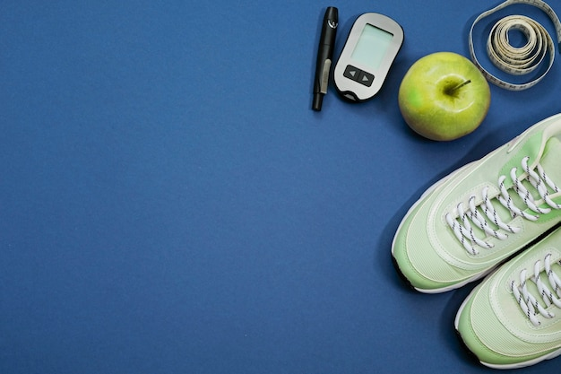 Flat lay with diet diabetes weight loss concept. sneakers, tape measure, glucometer on a blue