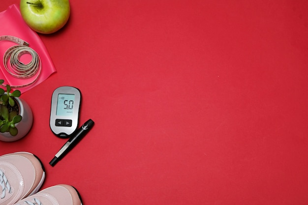 Flat lay with diet diabetes weight loss concept. sneakers, tape measure, glucometer on a red