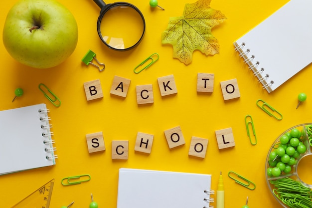 Flat lay with different school supplies and inscription back to school notebooks pen paper clips