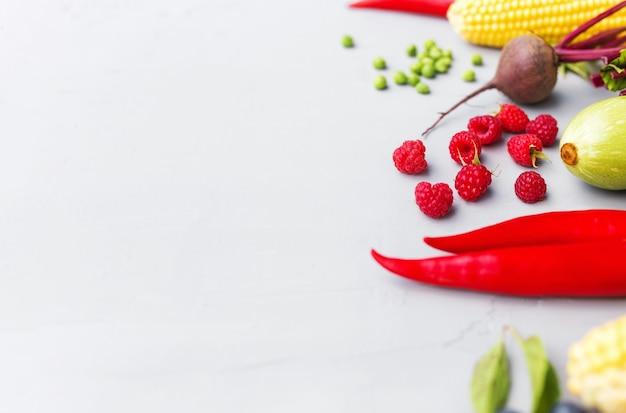 Плоская кладка с разными овощами, фруктами, ягодами, орехами, специями, зеленью, оливковым маслом. скопируйте пробел для текста. овощи на сером фоне бетона. концепция здорового питания органических био-продуктов