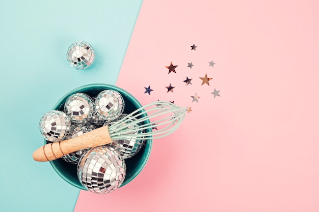 Flat lay with disco balls in the bowl with whisk.
