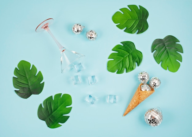 Flat lay with disco balls in the cone, ice cubes, cocktail glass