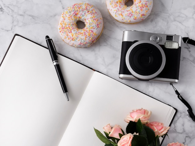 Flat lay with donuts, flowers, camera and notepad on white marble