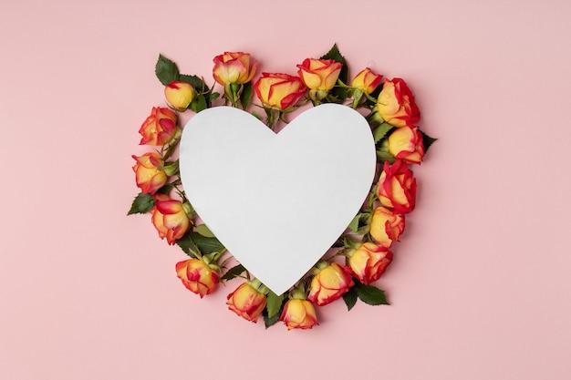 空のハート型のグリーティングカードとピンクの背景にバラ、モックアップでフラットレイ。バレンタイン・デー
