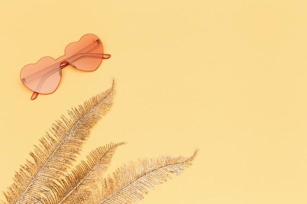 노란 종이에 패션 안경 핑크 컬러와 황금 야자 잎 플랫 누워