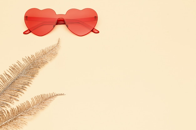 Flat lay with fashion glasses red colored and golden palm leaves on yellow paper. heart shaped eyeglasses. trendly summer background with copy space.