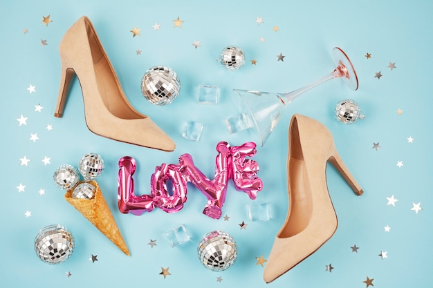 Flat lay with femail shoes, disco balls in the cone and cocktail glass