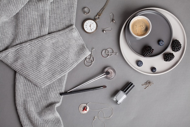 Flat lay with female accessories in gray shades