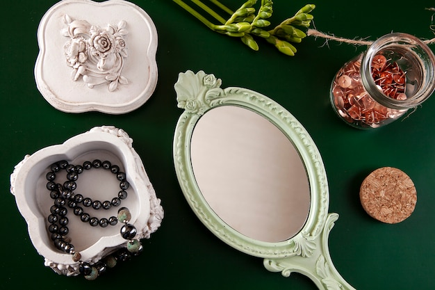 Flat lay with female accessories. necklace of pearls in a casket, mirror and a flower on a green