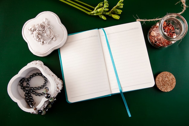 Flat lay with female accessories necklace of pearls in a casket, an open notebook and a flower on a green