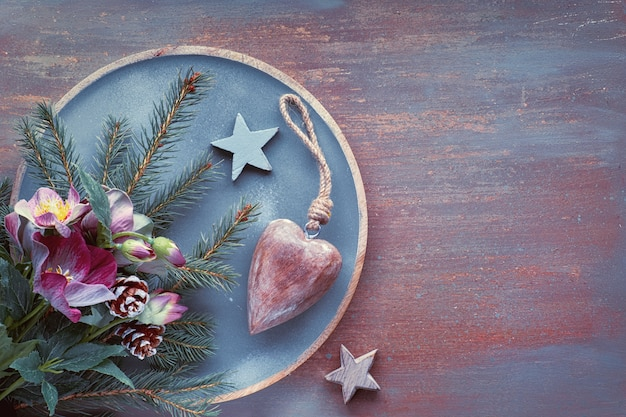 Flat lay with fir twigs, anemone flowers, wooden heart and star on textured surface