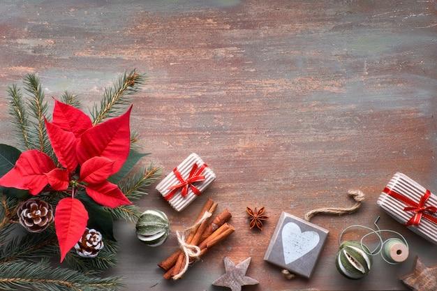 コピースペースと織り目加工の背景にフラットはモミの小枝、ポインセチア、クリスマスの装飾で横たわっていた。
