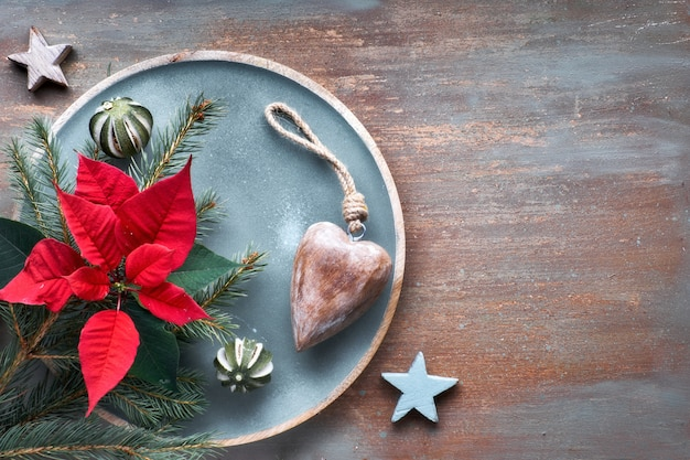 Flat lay with fir twigs, poincettia and xmas decorations on textured background