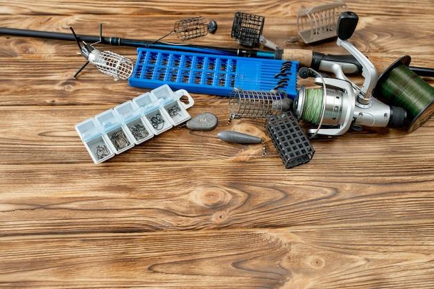 釣り道具、釣り竿、釣り道具とフック付きのプラスチックの箱、木の板のフィーダー、コピースペースを備えたフラットレイ。