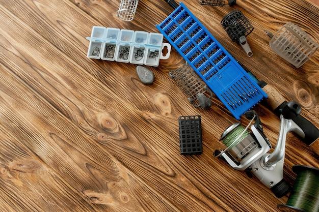 낚시 도구, 낚싯대 및 낚시 도구 및 후크가있는 플라스틱 상자가있는 평평한 누워, 나무 판자에 피더, 복사 공간