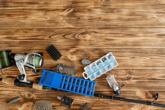 낚시 도구, 낚싯대 및 낚시 도구와 후크가있는 플라스틱 상자, 나무 판자 위의 피더가있는 평평한 누워