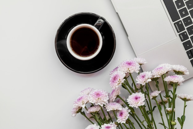 Flat lay with flowers and laptop with cup of coffee