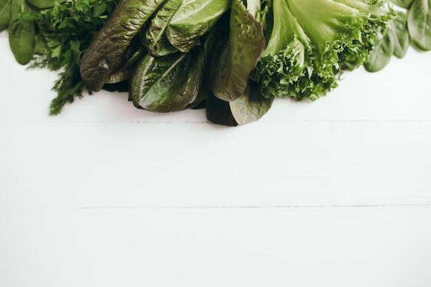 Плоская кладка со свежими зелеными листьями салата из шпината, салата, романа. концепция здорового вегетарианского питания.