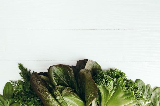 Квартира лежала со свежими зелеными листьями салата из шпината, салата, романа на белом фоне. концепция здорового питания