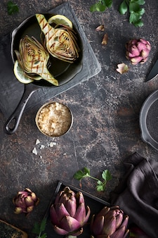 Flat lay with fresh and grilled red artichokes, while and halved, on dark