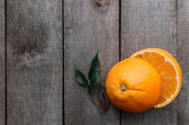 灰色の木製の背景にオレンジ色の果実の新鮮な熟したスライスされた半分で平らに横たわっていた。