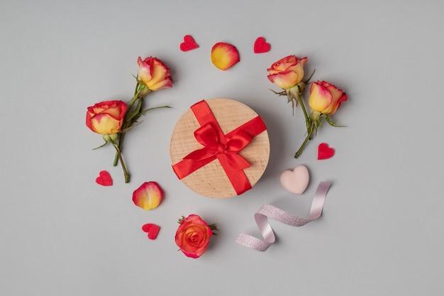 灰色の背景にギフトボックスとバラのフラットレイ。バレンタインや女性の日を祝う