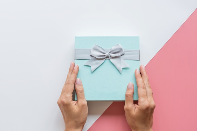 Flat lay with hands and gift box
