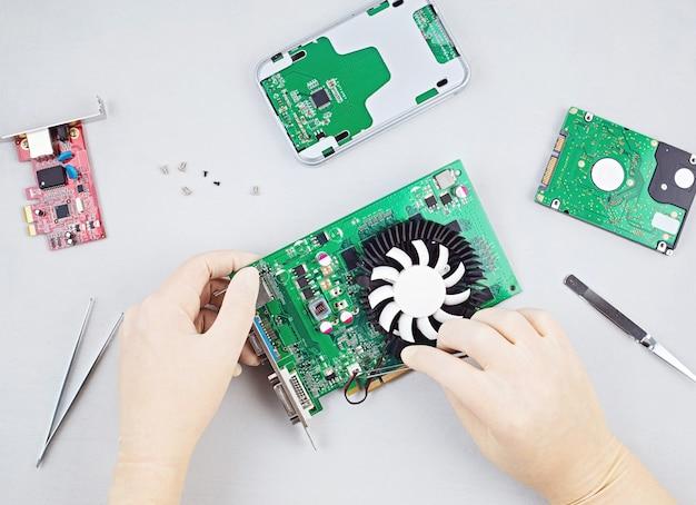 ビデオカードを修理するpcの電子部品に取り組んでいるエンジニアの手でフラットレイ。中小企業、コンピューター修理コンセプトの職場。上面図