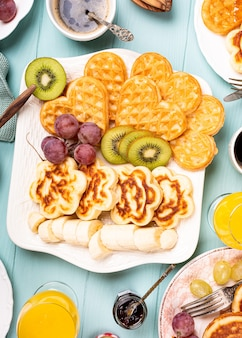 Flat lay with healthy breakfast with fresh hot waffles hearts, pancakes flowers with berry jam and fruits on turquoise surface, top view, flat lay. food concept