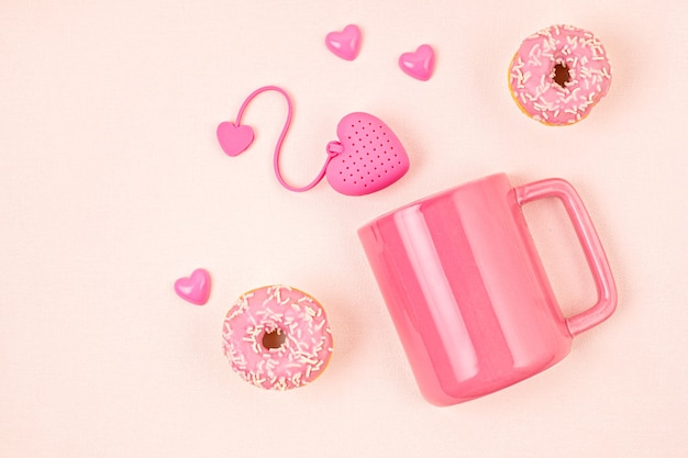 ハート型のティーバッグ、ドーナツ、カップが付いたフラットレイ。目を覚ます、朝のお茶、毎日の儀式、禅の態度、ストレス、健康的な飲み物、愛の概念