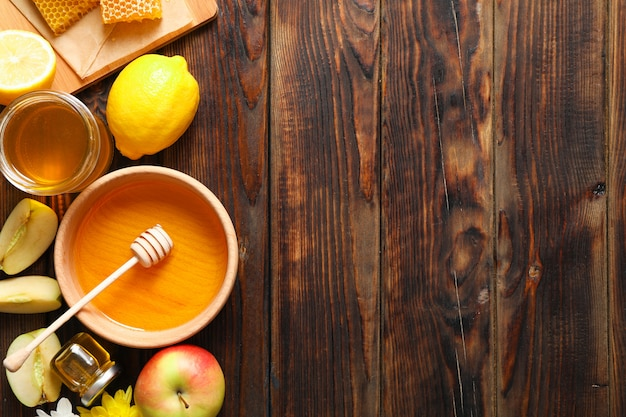 Flat lay with honey, flowers and fruits on wooden background, space for text