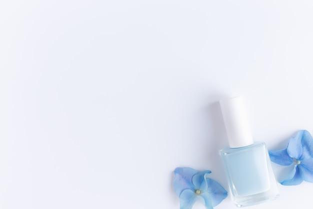 투명한 유리 병에 파란색 매니큐어가있는 hortensia 파란색 꽃잎이있는 평면 배치. 천연 매니큐어 및 페디큐어 개념