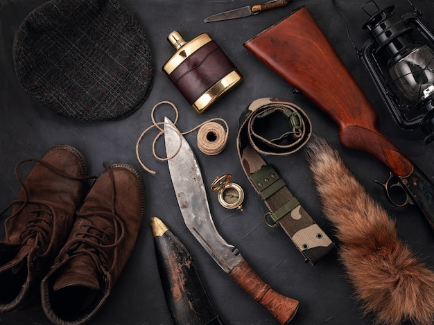Flat lay with hunting accessories over the grey surface: old boots, hat, rifle, knives, rope, belt, fox tail.