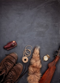 Flat lay with hunting ammunition over the grey background: old boots, rifle, knife, rope, belt, fox tail.