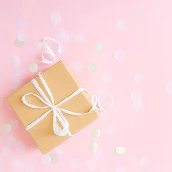 리본, 스타 및 원형 종이 색종이 또는 반짝이로 묶인 고립 된 공예 종이 선물 상자가있는 평면 누워