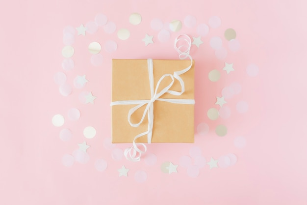Flat lay with isolated craft paper gift box tied with ribbon, star and circle paper confetti or glitters on pink pastel background.
