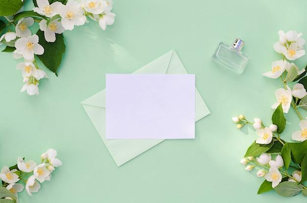 Плоская кладка с цветами жасмина, конверт с письмом и флакон духов.