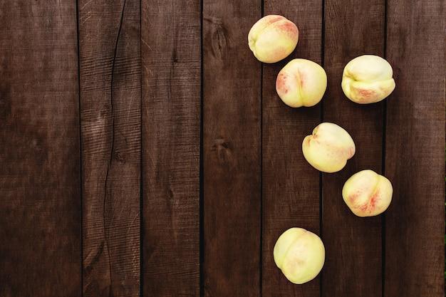 Квартира лежала с большой и большой группой сочных органических персиков на фоне коричневого деревянного стола со старыми досками. натуральные фрукты, копия пространства. фото высокого качества