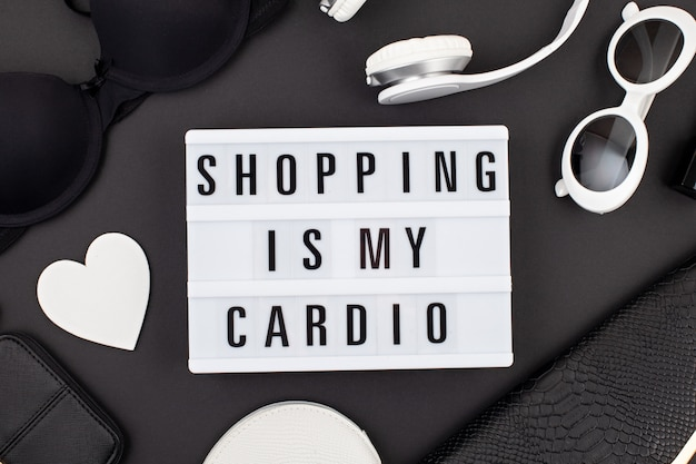 Flat lay with lightbox and funny quote shopping is my cardio